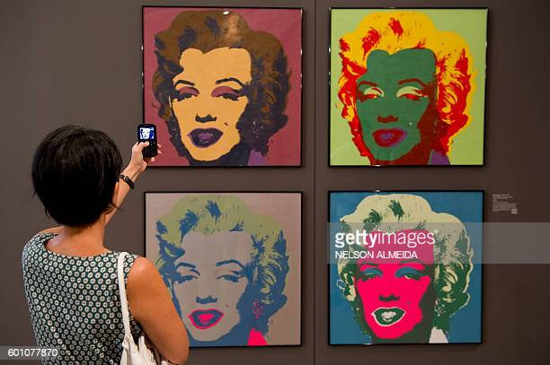 A visitor takes a picture of paintings from Andy Warhol's series Marilyn Monroe 1967 during the I want to be Marilyn Monroe exhibition at the...
