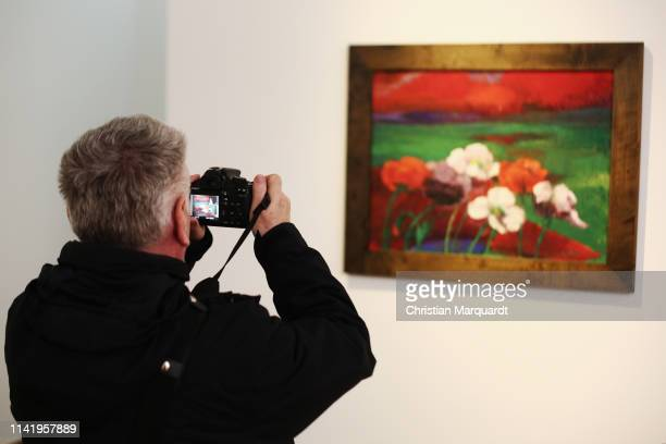 """Visitor takes a picture of the artwork 'Poppies And Red Evening Clouds' during the preview of the exhibition """"Emil Nolde - Eine deutsche Legende. Der..."""