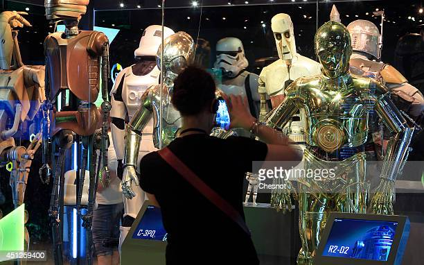 A visitor takes a picture of the costume of character from the Star Wars film series which are displayed during the exhibition Star Wars Identities...