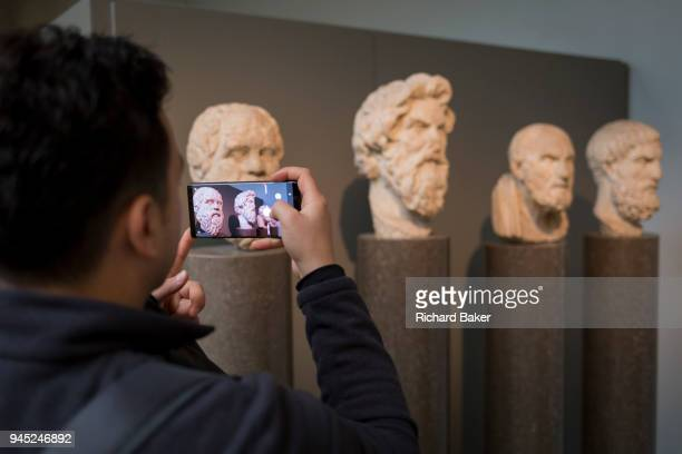 A visitor takes a picture of the heads of ancient Greek Hellenistic philosophers Sokrates Antisthenes Chrysippus and Epikouros in the British Museum...