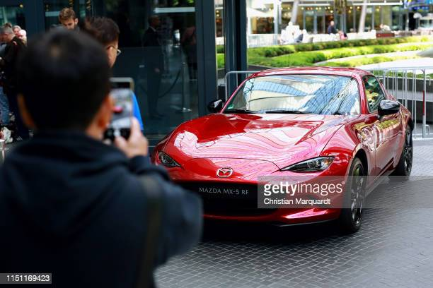 A visitor takes a picture of the Mazda MX5 RF by using a smartphone during the Mazda Spring Cocktail at Sony Centre on May 23 2019 in Berlin Germany