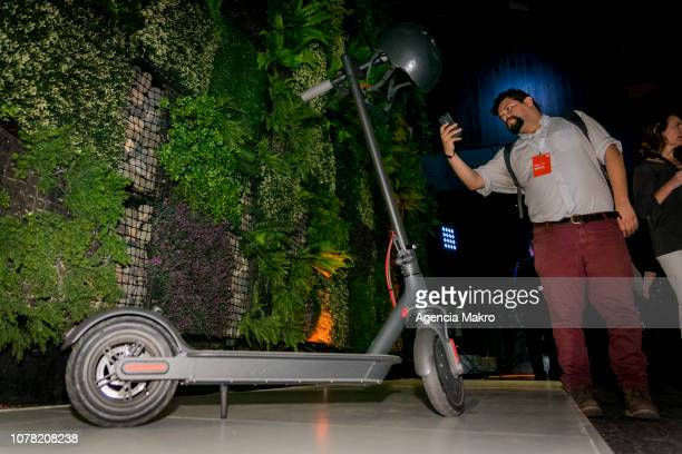 A visitor takes a picture of the Mi Electric Scooter during the official launch of the Chinese brand Xiaomi on December 05 2018 in Santiago Chile