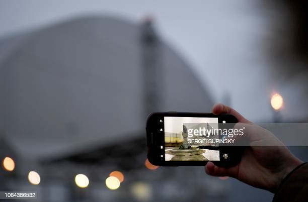 A visitor takes a picture of the New Safe Confinement measuring 108 metres in height and covering the 4th block of the Chernobyl Nuclear Power Plant...