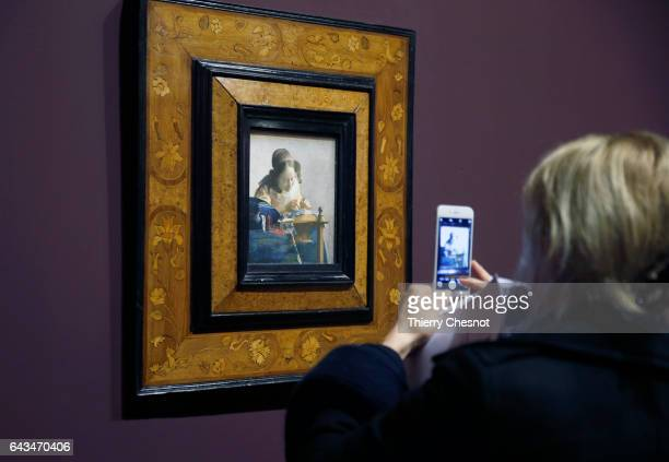 A visitor takes a picture of the painting 'The Lacemaker' by Dutch painter Johannes Vermeer during a press visit of the exhibition 'Vermeer and the...