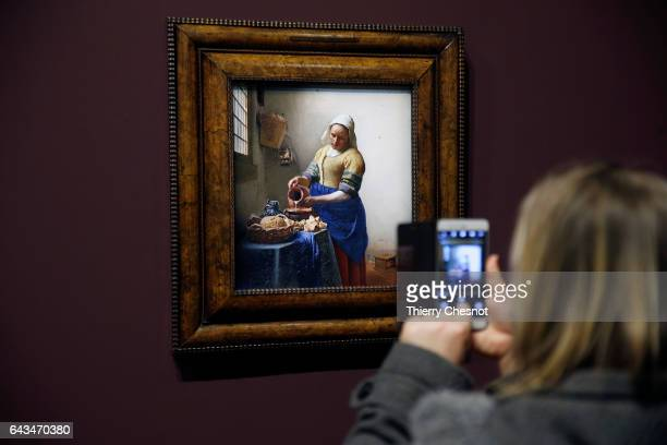 A visitor takes a picture of the painting 'The Milkmaid' by Dutch painter Johannes Vermeer during a press visit of the exhibition 'Vermeer and the...