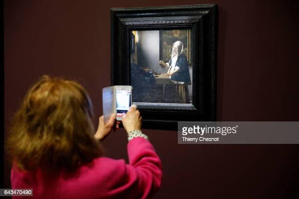 A visitor takes a picture of the painting 'Woman with the balance' by Dutch painter Johannes Vermeer during a press visit of the exhibition 'Vermeer...