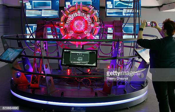 A visitor takes a picture of the 'portail Tesseract' during the 'Marvel Avengers STATION' exhibition at La Defense on April 12 2016 in Paris France...