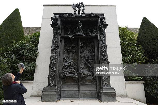 A visitor takes a picture of the sculptural group 'The Gates of Hell' by French sculptor Auguste Rodin at the Hotel Biron housing the Musee Rodin in...