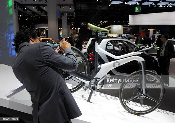 A visitor takes a picture of the Smart eBike presented at the Paris Auto Show on October 1st 2010 The show will open to the public on October 2nd...