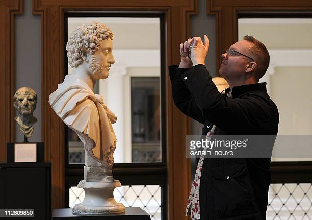 A visitor takes a picture on April 18 2011 of a bust of Roman Emperor Commodus at the Getty Villa Museum in Malibu California AFP PHOTO / GABRIEL...
