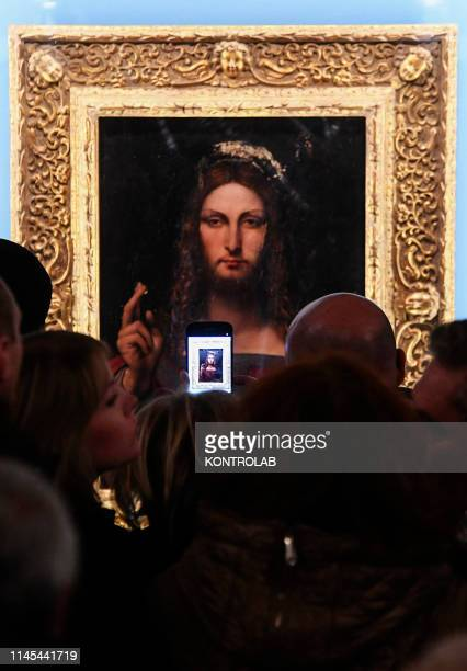 Visitor takes a picture with a mobile phone in Naples at a showing of the Salvator Mundi, an alleged painting by Leonardo Da Vinci found in Naples,...