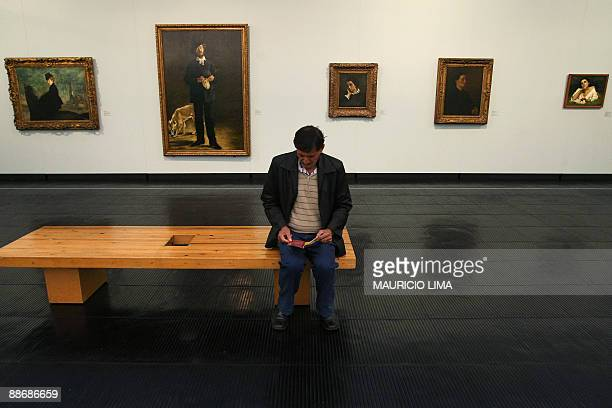 A visitor takes a rest in front of paintings by French artists Edouard Manet and Gustave Coubert during a retrospective exhibition Art in France1860...