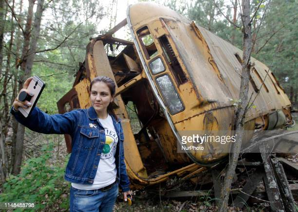 A visitor takes a selfie in front of a wreckage bus in the abandoned city of Pripyat near the Chernobyl nuclear power plant Ukraine on 7 June 2019The...