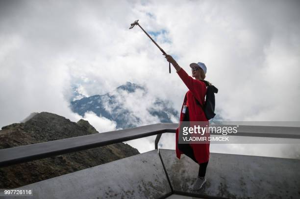 A visitor takes a selfie on July 11 2018 on the terrace of the James Bond cinematic installation named '007 ELEMENTS' at the top of the Gaislachkogl...