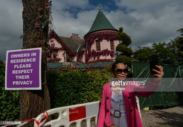Visitor takes a selfie outside the house in The Burnaby area of Greystones which has been covered from the roof down by stretched pink flowers and...