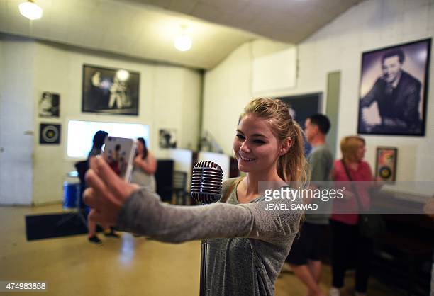 A visitor takes a selfie with a recording microphone during a tour of Sun Studio in Memphis Tennessee on May 28 2015 Sun Studio a recording studio...