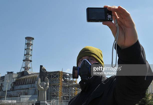 A visitor takes a selfportrait in front of the 4th power block of the Chernobyl Nuclear Power Plant on April 18 2011 In the heart of Chernobyl...