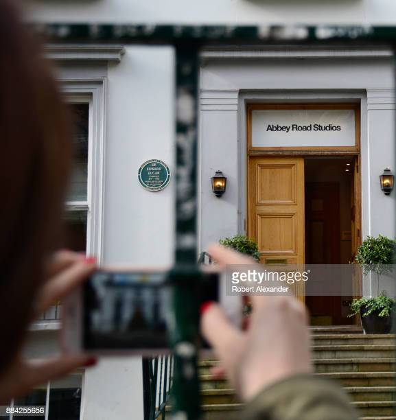 A visitor takes a souvenir photograph through the fence in front of Abbey Road Studios in London England Formerly known as EMI Studios the recording...