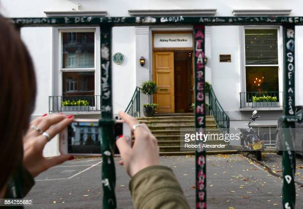 Visitor takes a souvenir photograph through the fence in front of Abbey Road Studios in London, England. Formerly known as EMI Studios, the recording...