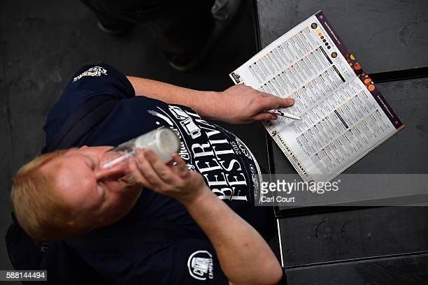 A visitor takes a swig of ale as he makes notes at the CAMRA Great British Beer festival at Olympia London exhibition centre on August 10 2016 in...