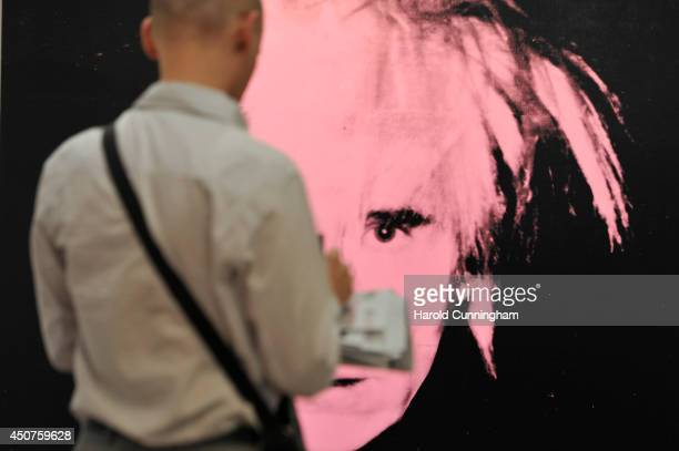 A visitor takes notes in front of the artwork 'SelfPortrait' by Andy Warhol in the gallery section of Art Basel on June 17 2014 in Basel Switzerland...