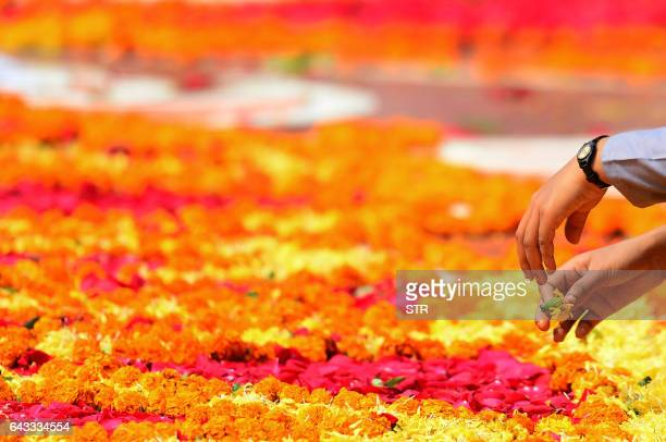 A visitor takes part in the making of a floral tribute at the Bangladesh Central Language Martyrs' Memorial monument in Dhaka on February 21 on...