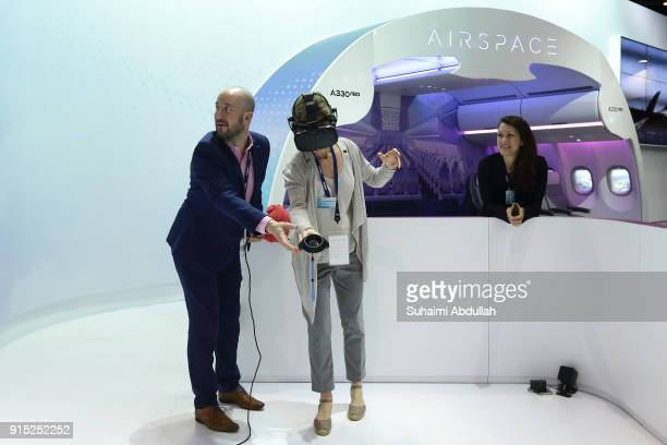 A visitor takes part in the virtual reality experience at the Airbus booth during the Singapore Airshow at Changi Exhibition Centre on February 7...