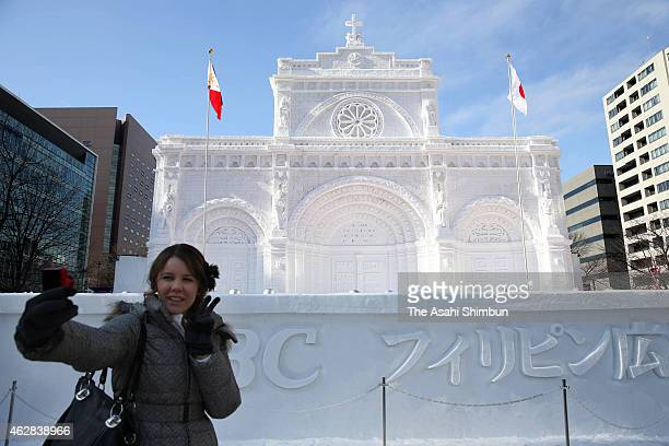A visitor takes photographs in front of a snow statue during the 66th Sapporo Snow Festival at Odori Park on February 6 2015 in Sapporo Japan The...