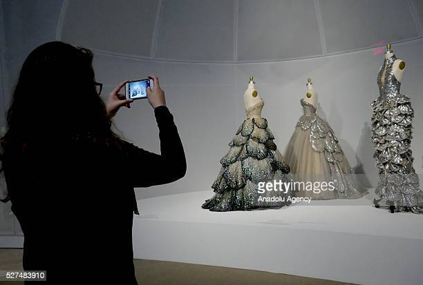 A visitor takes photographs of dresses during the 'Manus x Machina Fashion In An Age Of Technology' Costume Institute Gala at Metropolitan Museum of...