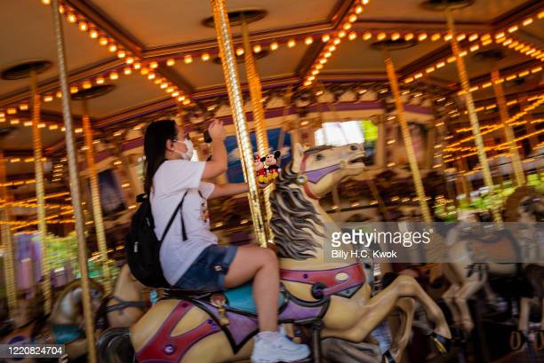 A visitor takes photographs of Mickey and Minnie Mouse as she rides on carousel at Walt Disney Co's Disneyland Resort on June 18 2020 in Hong Kong...