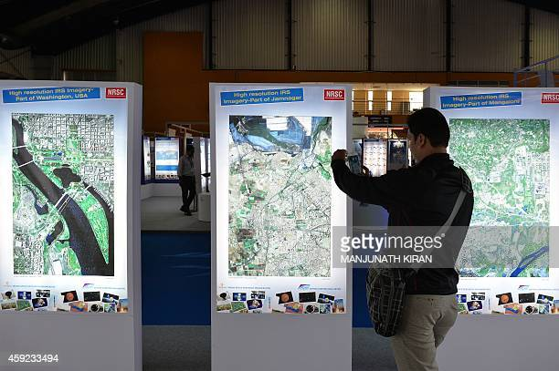 A visitor takes photographs of posters of satellite imaging on display at the Indian Space Research Organisation stall during the 4th edition of...