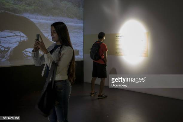 A visitor takes photographs with a mobile device inside the Museo Casa de la Memoria in Medellin Colombia on Tuesday Oct 3 2017 In Colombia where...