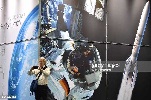 A visitor takes photos at the 68th International Astronautical Congress 2017 in Adelaide on September 28 2017 The 68th International Astronautical...