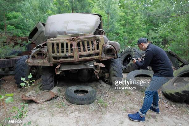 A visitor takes photos of a wrecked car at the Chernobyl exclusion zone in the abandoned city of Pripyat The HBO television miniseries Chernobyl...