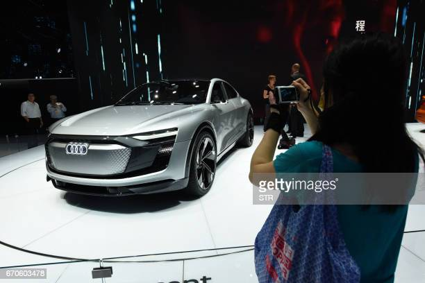 A visitor takes photos of an Audi etron Sportback Concept car displayed during the second day of the 17th Shanghai International Automobile Industry...