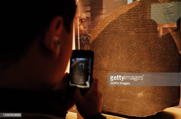 Visitor takes photos of the Rosetta Stone in the ancient Egypt section of the British Museum in London. The museum, one of London's top tourist...