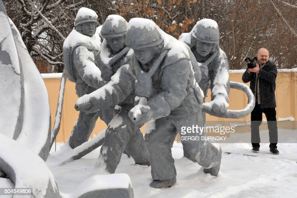 A visitor takes pictures at monument for dead firemen in the city of Chernobyl on February 22 2011 Today Ukraine's Emergency ministry started...