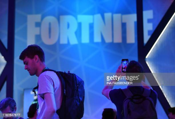 A visitor takes pictures at the stand of the Fortnite computer game at the media day of the Gamescom video games trade fair in Cologne western...