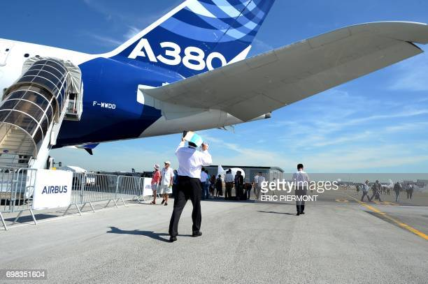 A visitor takes pictures in front of the Airbus A380 with the mention A380plus at Le Bourget on June 20 2017 during the International Paris Air Show...
