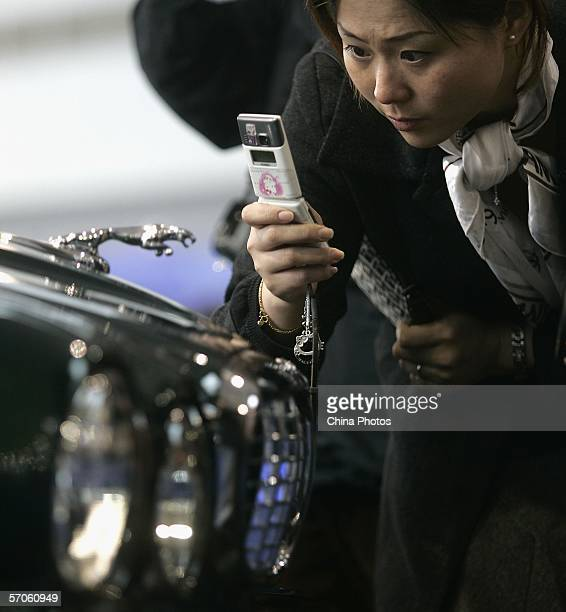 A visitor takes pictures of a Jaguar logo at the Imported Auto Expo Shanghai 2006 at the Shanghai Automobile Exhibition Center on March 11 2006 in...