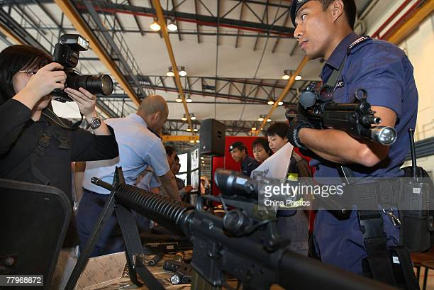 A visitor takes pictures of a member of Airport Security Unit during the Government Flying Service Open Day on November 18 2007 in Hong Kong China...