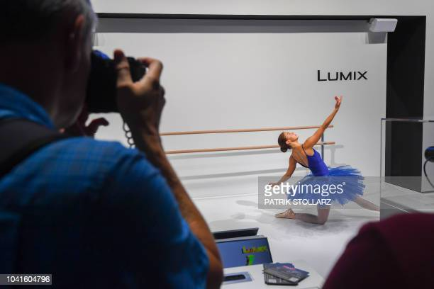 A visitor takes pictures of a model at the Panasonic stand at the Photokina trade fair in Cologne western Germany on September 27 2018 The fair for...