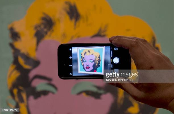 A visitor takes pictures of a work by US artist Andy Warhol depicting late US actress Marilyn Monroe during an exhibition of the legendary pop artist...