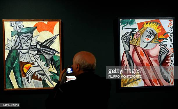 A visitor takes pictures of part of 'Queen of diamonds' and 'Jack of hearts' by Olga Vladivirovna Rozanova as part of the 'Russian AvantGardes'...