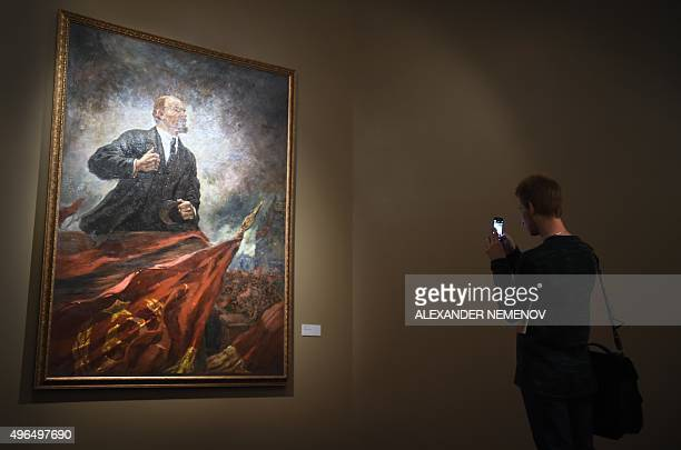 A visitor takes pictures of Soviet artist Aleksandr Gerasimovs painting Lenin on the Tribune displayed in the exhibition Romantic Realism Soviet Art...