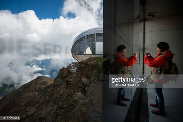 A visitor takes pictures of the view on July 11 2018 during a visit at the James Bond cinematic installation named '007 ELEMENTS' at the top of the...