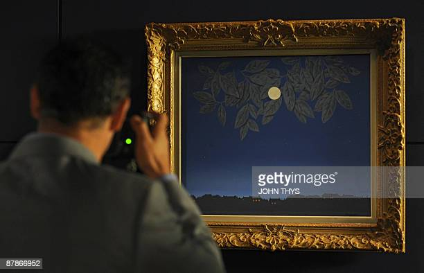 A visitor takes pictures of The White Page 1967 a painting by the Belgian artiste Rene Magritte displayed at the press opening of the new Magritte...