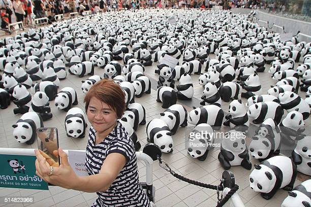 A visitor takes selfie with the 1600 Pandas exhibition by French artist Paulo Grangeon displayed in front of Bangkok Art Culture Centre These are...