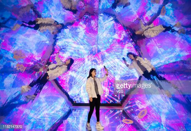 A visitor takes selfies in the 'Kaleidoscope' installation at an experience centre on May 27 2019 in Hohhot Inner Mongolia Autonomous Region of China