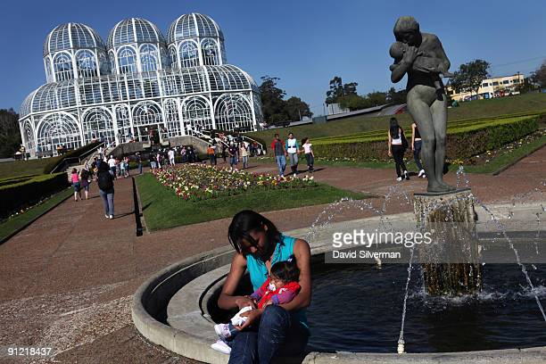 A visitor tends to a child in front of a statue in the Botanical Garden on August 15 2009 in Curitiba the capital city of the state of Parana Brazil...
